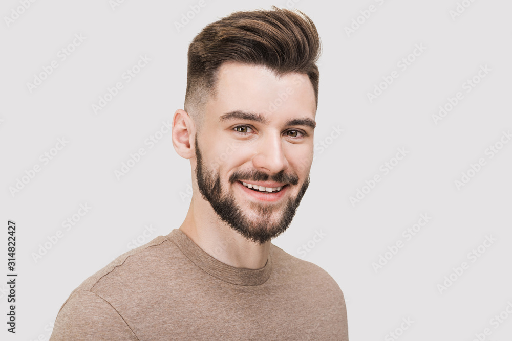Fototapeta Closeup portrait of handsome smiling young man. Laughing joyful cheerful men studio shot. Isolated on gray background