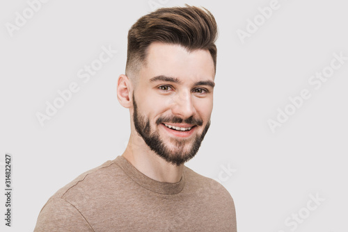 Obraz Closeup portrait of handsome smiling young man. Laughing joyful cheerful men studio shot. Isolated on gray background - fototapety do salonu