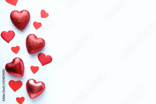 Fototapeta Valentine's, Mother's or Women's Day greeting card, banner or poster template. Holidays background with festive red heart shaped decorations and empty background with place for text design obraz