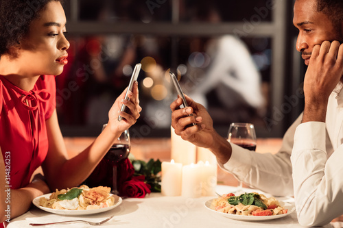 Obraz Bored African American Couple Using Phones During Date In Restaurant - fototapety do salonu