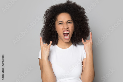 Photo Overjoyed african american young woman showing hard rock horns gesture