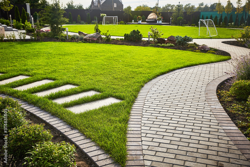 Fototapeta Landscaping of the garden. path curving through Lawn with green grass and walkway tiles.