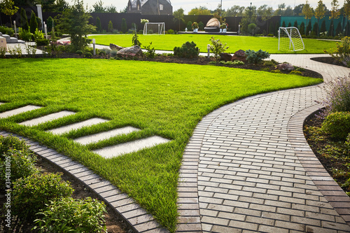 Fototapeta Landscaping of the garden. path curving through Lawn with green grass and walkway tiles. obraz