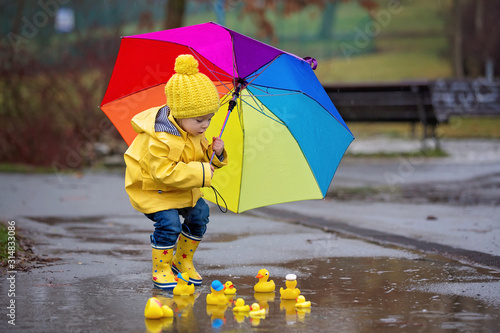 Beautiful funny blonde toddler boy with rubber ducks and colorful umbrella, jump Fototapet