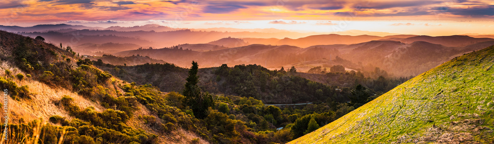 Fototapeta Expansive panorama in Santa Cruz mountains, with hills and valleys illuminated by the sunset light; San Francisco Bay Area, California