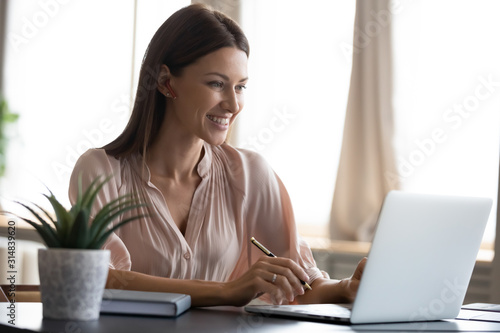 Smiling young woman work on laptop making notes Canvas Print