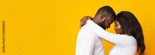 Valokuvatapetti Happily married black couple hugging over yellow background