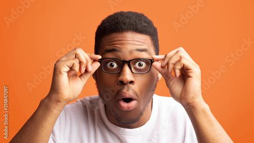 Valokuva Surprised african american guy touching his eyewear