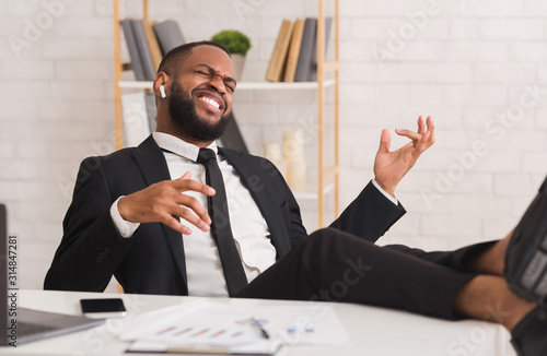 Young relaxed businessman listening to music at office