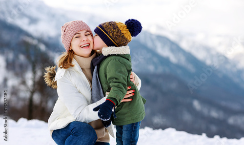 Obraz happy family mother and child playing on winter walk. - fototapety do salonu