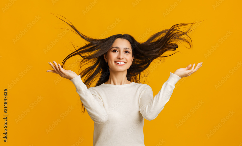 Fototapeta Portrait of beautiful brunette girl with flying hair over yellow background