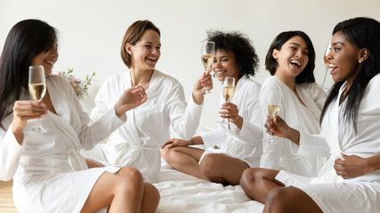 Smiling girls have fun drink champagne at hen party