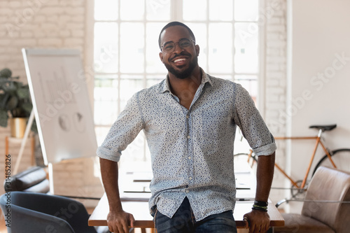 Obraz Portrait of smiling african American employee posing in office - fototapety do salonu