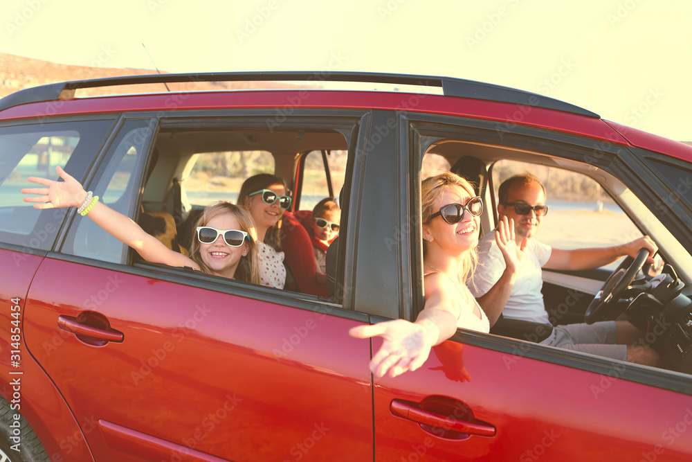 Fototapeta Happy smiling family with daughters in the car with sea background