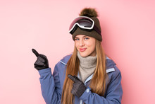 Skier Teenager Girl With Snowboarding Glasses Over Isolated Pink Background Pointing Finger To The Side