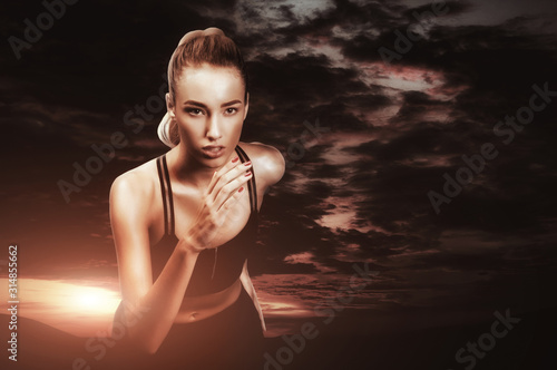 Fotografía  Young sporty woman jogging open air over sunset