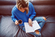 Leinwanddruck Bild - Top view of blond caucasian young woman in sweater sitting on sofa in living room, drinking coffee and reading book.