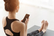 Girl using phone after practicing yoga on mat