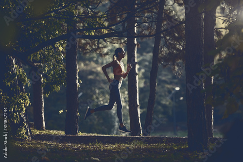 Side view of slim attractive caucasian brunette in sportswear and with ponytail running on trail in woods.