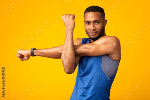 Healthy black guy stretching hand and shoulder before workout Wallpaper Mural