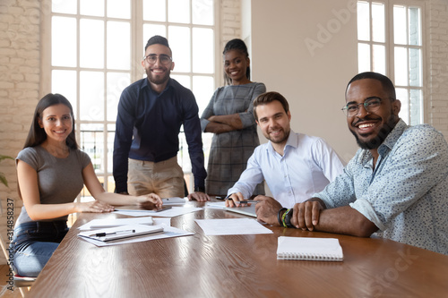 Valokuvatapetti Multiethnic smiling employees gather at boardroom meeting