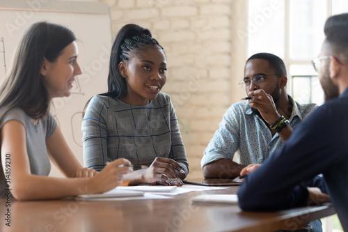 Fototapeta Multiethnic employees talk discussing ideas at meeting