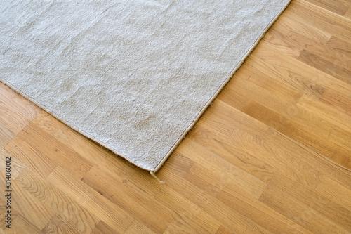 Fototapeta Close up of crumpled carpet laying on parquet wooden floor. obraz na płótnie