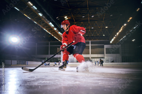 Obraz Dedicated strong caucasian handsome hokey player playing hockey on ice in hall. - fototapety do salonu