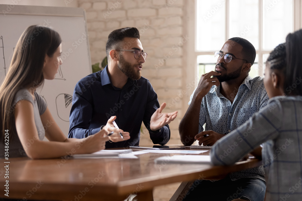 Fototapeta Thoughtful millennial diverse colleagues discuss ideas at briefing