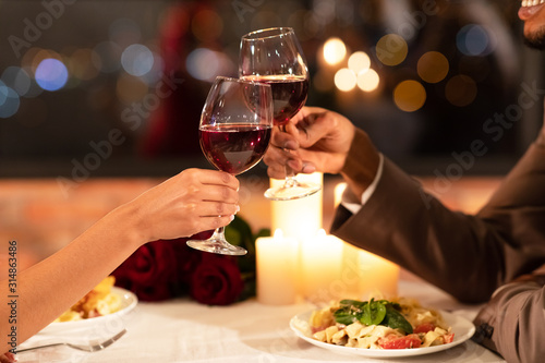 Vászonkép Couple's Hands Clinking Glasses Of Red Wine Dating In Restaurant