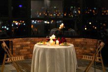 Served Table With Food And Burning Candles In Restaurant Interior