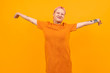 Unusual pretty woman with short pink hair and tattoo smiles isolated on orange background