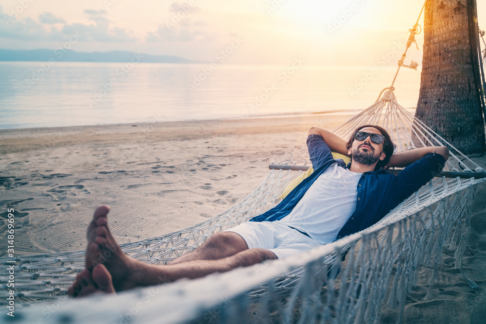 Fototapeta Young handsome Latin man in sunglasses relaxing in a hammock on the beach at sunset on the beach.