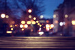 background Image of wooden table in front of street view in front of abstract blurred lights