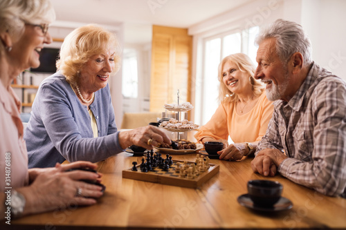 Fototapeta Happy senior people playing chess while relaxing at home. obraz
