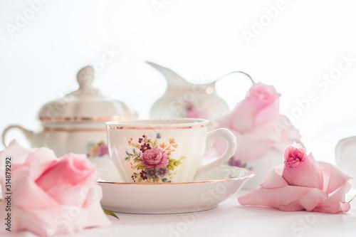Fototapeta A set of  floral rose pattern fine china porcelain tea set with a tea-pot, sugar pot, creamer, and tea cup obraz