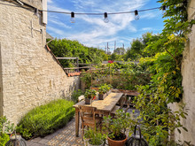 Small Walled Urban Garden Full With Green Plants And Wooden Furniture In Summer During Sunrise