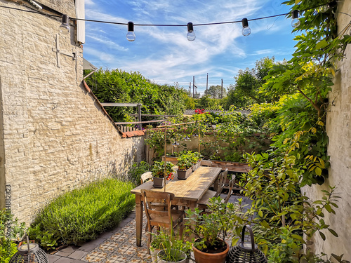 Fotografía Small walled urban garden full with green plants and wooden furniture in summer