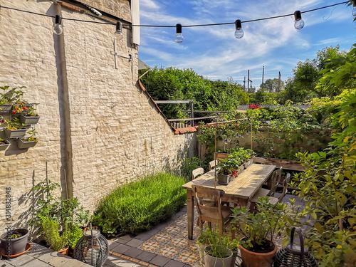 Small walled urban garden full with green plants and wooden furniture in summer Billede på lærred