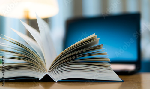 Fotografie, Obraz Open book lying on the table in the library