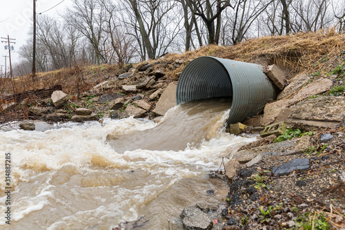 Vászonkép Closeup motion blur of storm water runoff flowing through metal drainage culvert under road