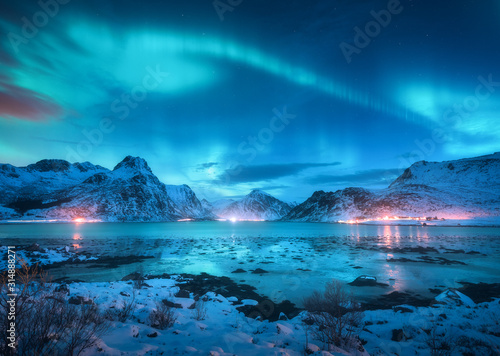 Photo Aurora borealis over the sea coast, snowy mountains and city lights at night