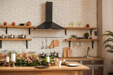 Christmas kitchen decor and copy space. Rustic cuisine at Christmas. Details of scandinavian cuisine in bronze color. Kitchen island table with festive table setting.