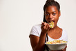 Studio portrait of a funny young African woman eating a salad. Fresh fruits and healthy diet concept.
