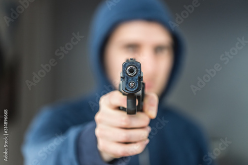 Fototapeta Crime or robbery concept: Man with black gun is aiming with his weapon obraz