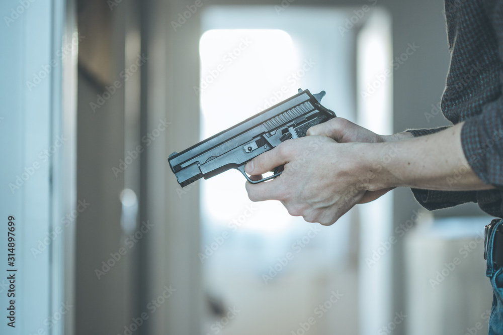 Fototapeta Police undercover weapon concept: Man is holding black weapon in his hand