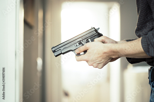 Fototapeta Police undercover weapon concept: Man is holding black weapon in his hand obraz