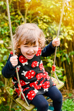 Adorable Little Girl Playing In The Garden With Her Swing