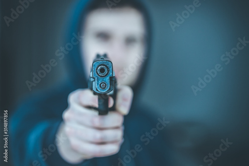 Crime or robbery concept: Man with black gun is aiming with his weapon Wallpaper Mural
