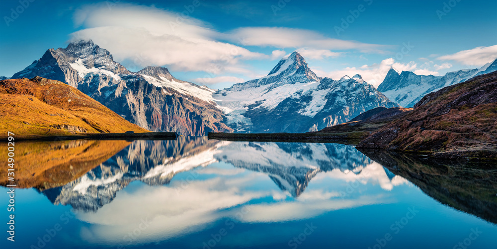 Panoramic morning view of Bachalp lake / Bachalpsee, Switzerland. Majestic autumn scene of Swiss alps, Grindelwald, Bernese Oberland, Europe. Beauty of nature concept background.